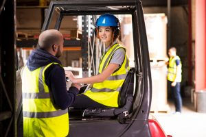 female forklift driver chatting to training supervisor