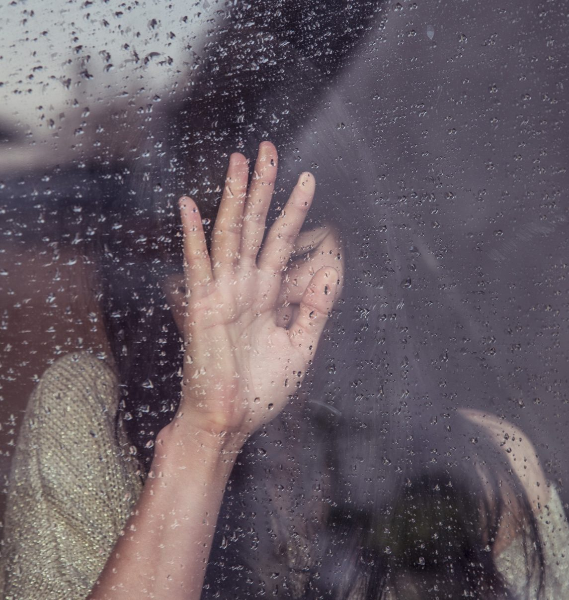 Woman devastated over a rainy window