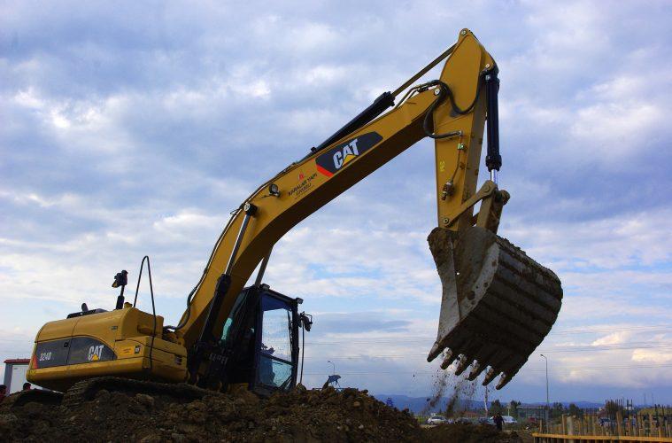 Tracked excavator on mound of soil